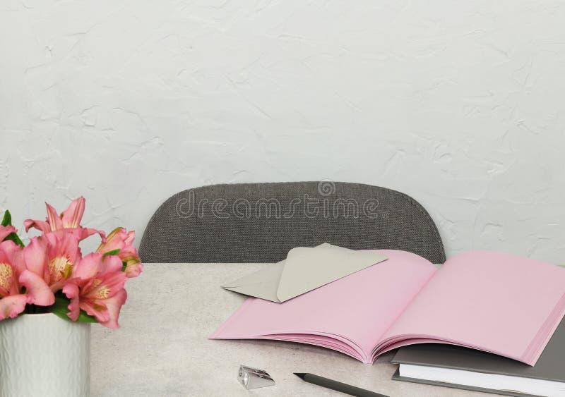 桃红色笔记,书,信封,在灰色书桌上的花 库存照片