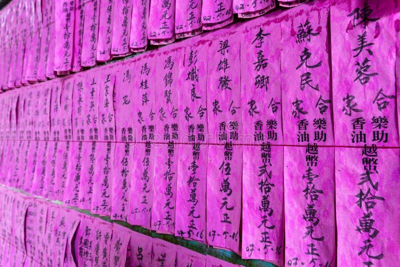 桃红色纸祷告旗子或滑动与名字在中国贷方在Cho Lon,第5区,西贡,越南Thien赫乌寺庙  免版税库存照片