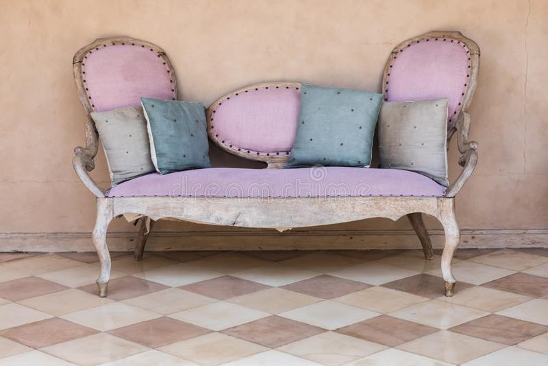 桃红色纺织品葡萄酒沙发 库存图片