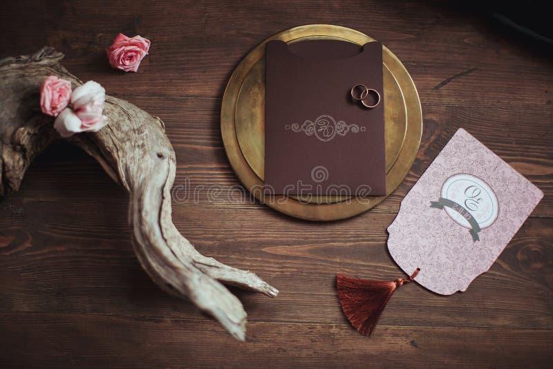 桃红色美好的婚礼的形象艺术和棕色卡片,有两个圆环的金黄板材在木背景 玫瑰,断枝 顶层 库存图片
