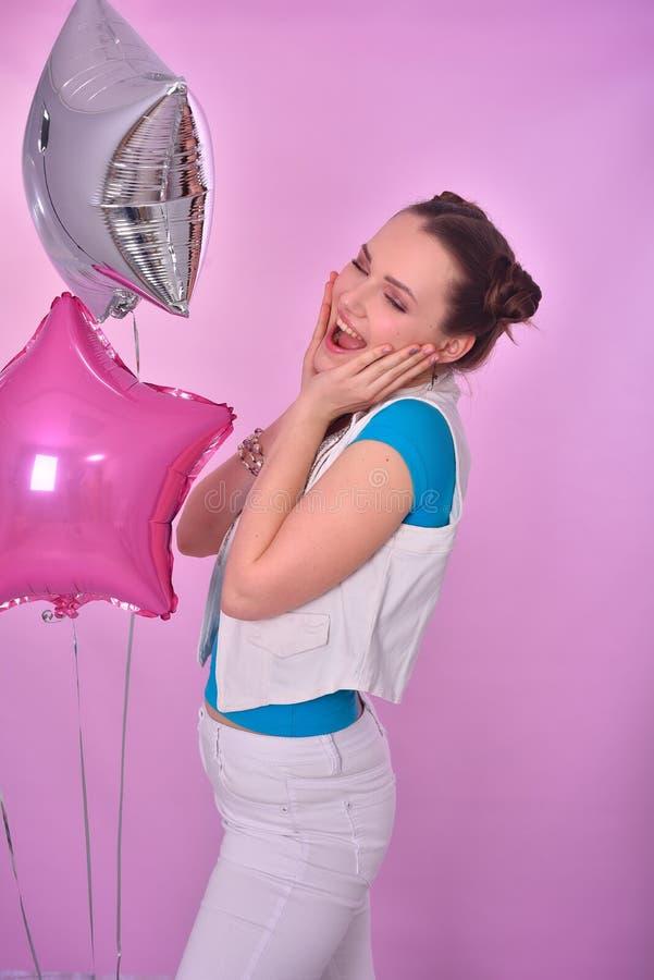 桃红色背景的女孩与气球 库存图片