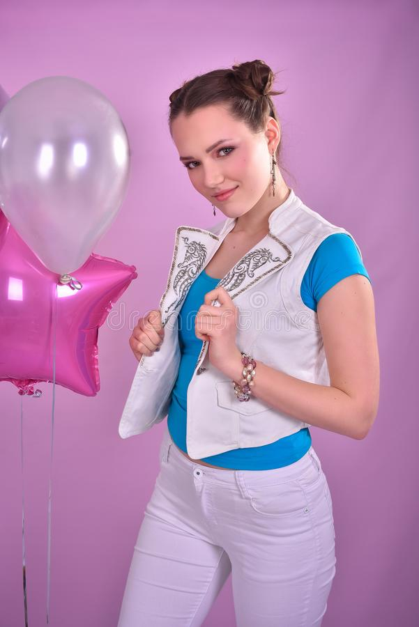 桃红色背景的女孩与气球 免版税图库摄影