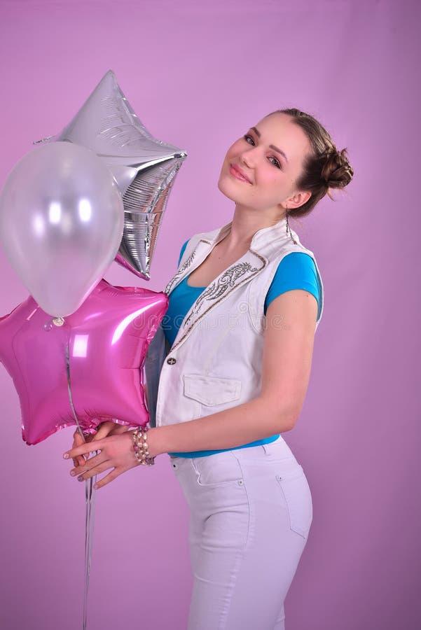 桃红色背景的女孩与气球 免版税库存照片