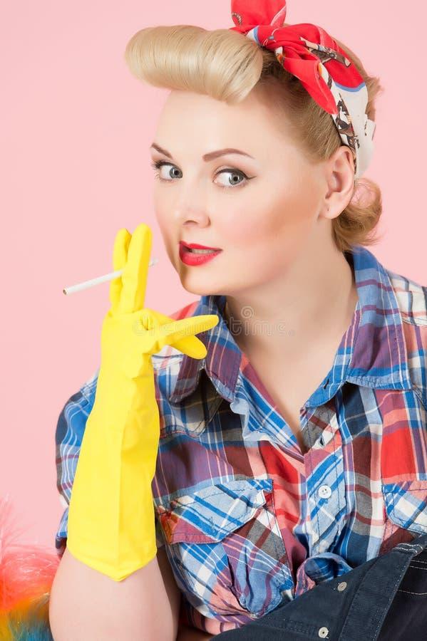 桃红色背景的白肤金发的女孩 夫人在手上拿着香烟有橡胶手套的 主妇抽烟的断裂 免版税库存图片