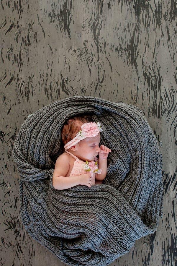 桃红色背景的睡觉的新出生的女孩 新出生的Photoshoot 从诞生的20天 画象美丽,七天 免版税库存照片