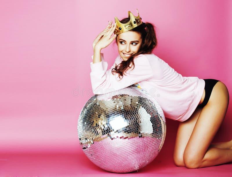 桃红色背景的年轻逗人喜爱的迪斯科女孩与迪斯科球和阴级射线示波器 图库摄影