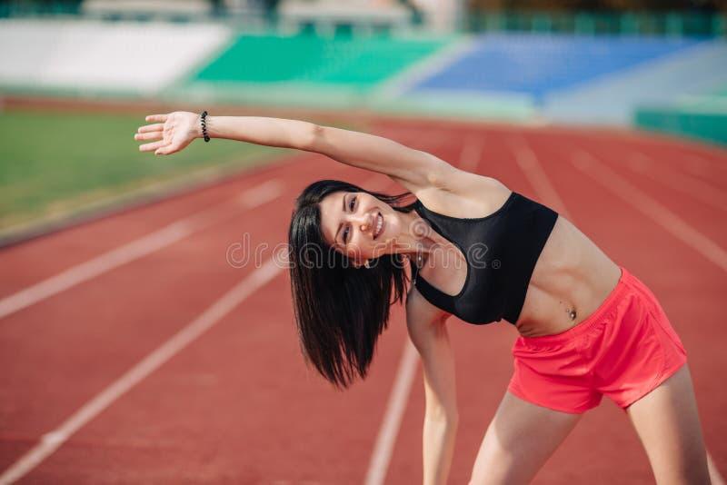 桃红色舒展在体育体育场的短裤和顶面锻炼的运动员可爱的运动的深色的妇女在晚上,日落 体育和 免版税库存图片