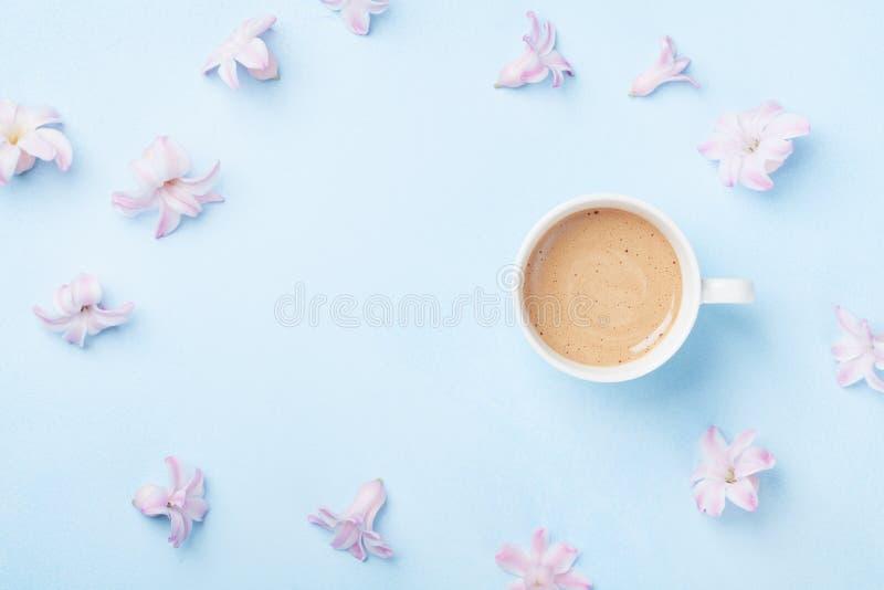 桃红色花和咖啡在蓝色淡色背景顶视图 创造性和时尚构成 平的位置样式 免版税库存照片