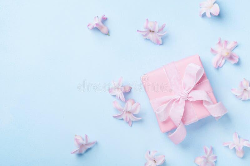 桃红色花和礼物或者礼物盒在蓝色淡色台式视图 贺卡为3月8日、妇女或者母亲节 平的位置 免版税库存图片