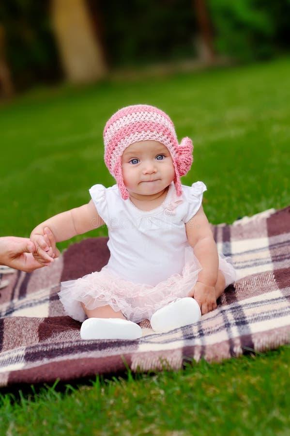 桃红色花帽子和芭蕾舞短裙的美丽的4个月大女婴 免版税库存照片