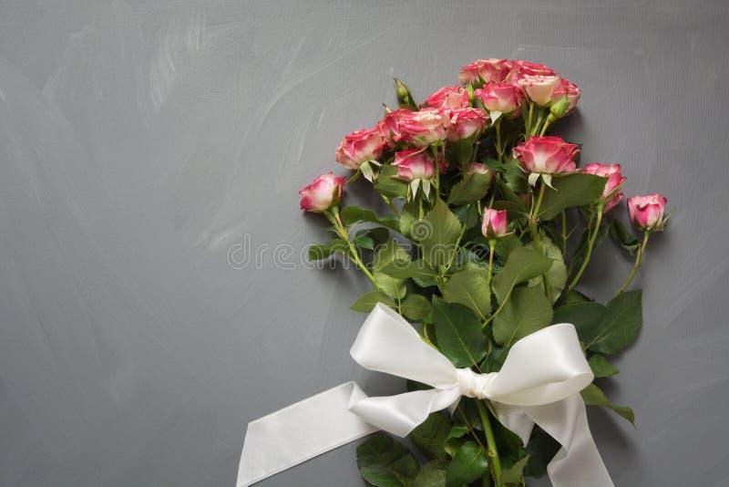 桃红色花束察觉了与白色丝带的灌木玫瑰在灰色背景 顶视图 充满爱的浪漫卡片 库存照片