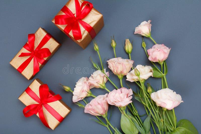 桃红色花花束与叶子和礼物盒的有在灰色背景的红色丝带的 顶视图 库存图片