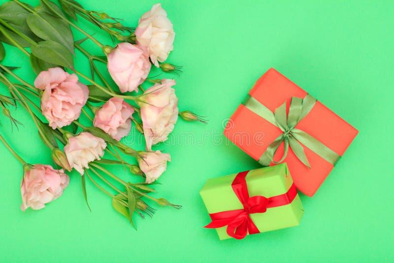 桃红色花花束与叶子和礼物盒的有在绿色背景的丝带的 图库摄影