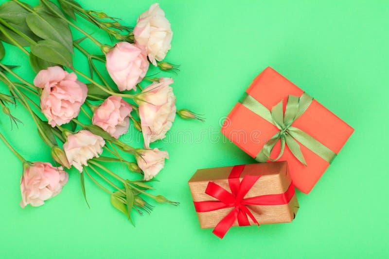 桃红色花花束与叶子和礼物盒的栓与在绿色背景的丝带 库存照片