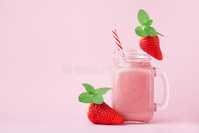 桃红色草莓圆滑的人或奶昔在金属螺盖玻璃瓶装饰了薄菏在淡色背景 早餐和快餐的健康食物 库存图片