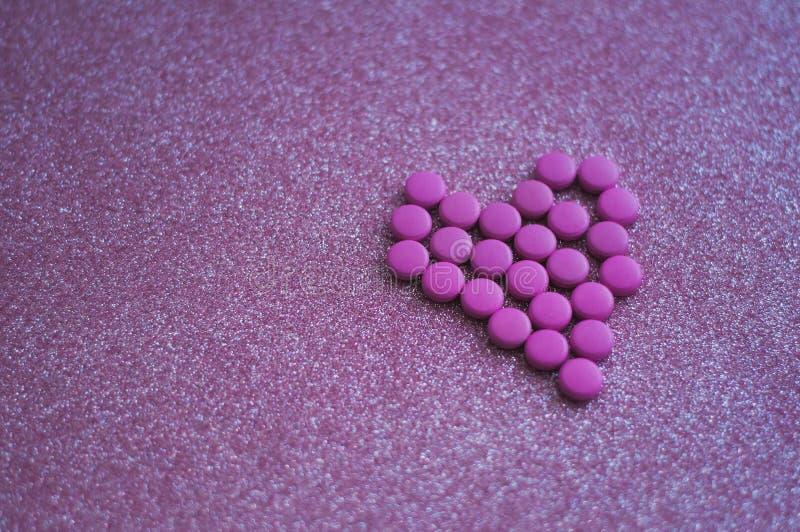 桃红色药片在心脏的形状计划了在闪烁桃红色背景的 免版税库存照片