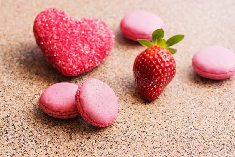 桃红色蛋白杏仁饼干用新鲜的草莓和红色糖心脏 日s华伦泰 选择聚焦 图库摄影