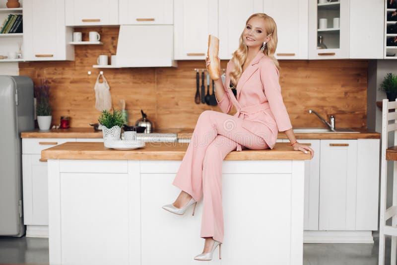 桃红色衣服的华美的白肤金发的妇女用面包在厨房countrer的 库存照片