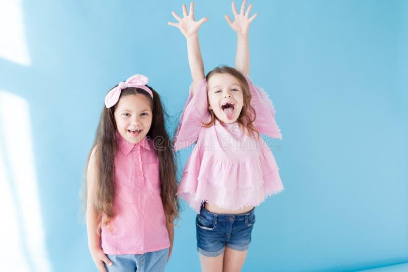 桃红色衣物女朋友的两女孩笑 免版税库存图片