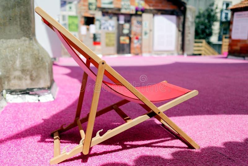桃红色表面上的空的轻便折叠躺椅 免版税库存照片