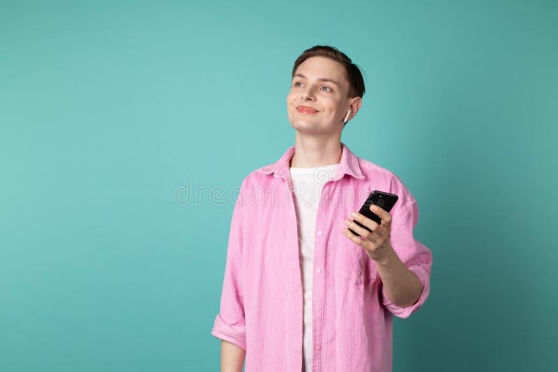 桃红色衬衣的年轻帅哥有电话的在手和白色耳机上 免版税库存照片