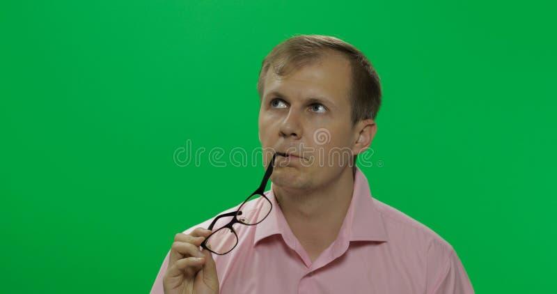 桃红色衬衣的英俊的体贴的人考虑某事 o 免版税库存照片