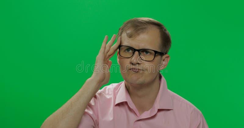 桃红色衬衣的英俊的体贴的人考虑某事 o 库存照片