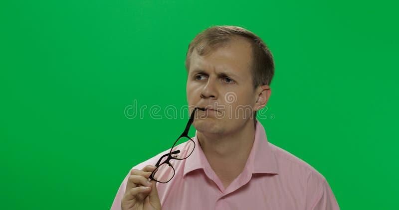 桃红色衬衣的英俊的体贴的人考虑某事 o 库存图片