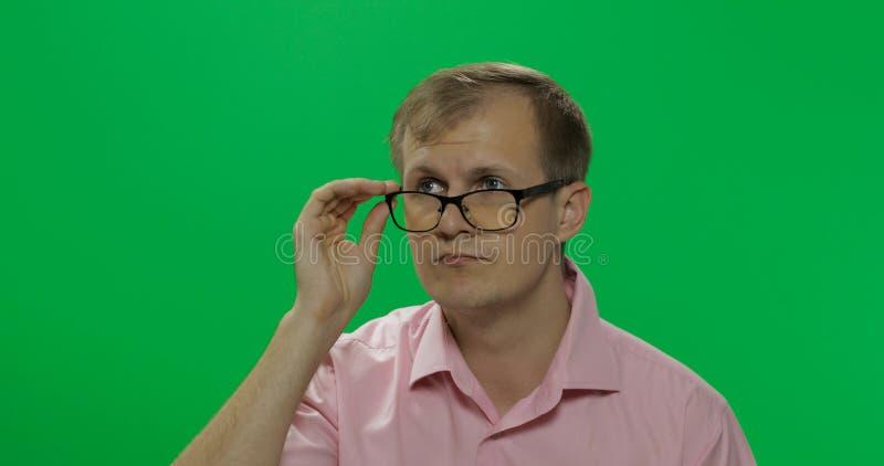 桃红色衬衣的英俊的体贴的人考虑某事 o 免版税库存图片