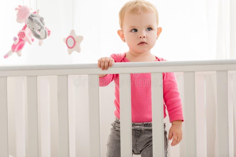 桃红色衬衣身分的可爱的孩子在小儿床和 库存照片