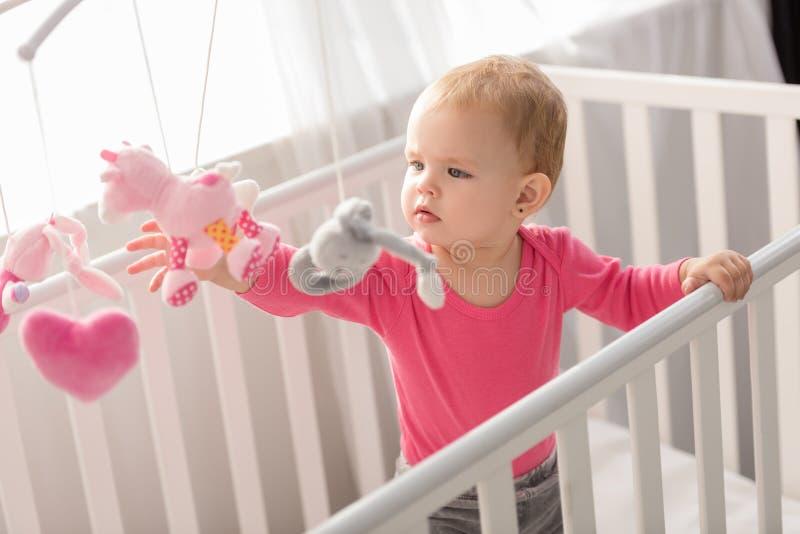 桃红色衬衣身分的可爱的孩子在小儿床和 库存图片