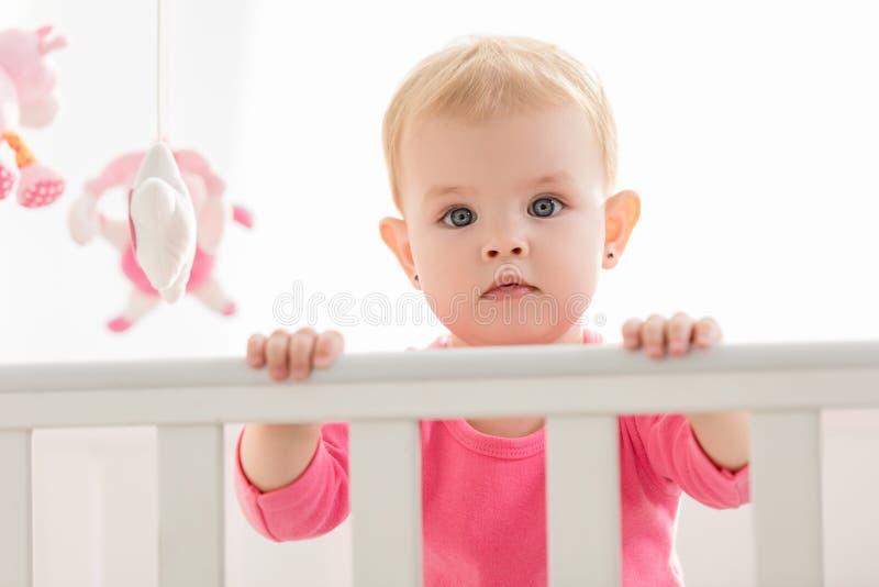 桃红色衬衣身分的可爱的小孩在小儿床和看 图库摄影