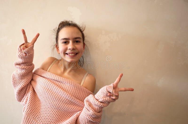 桃红色被编织的毛线衣的十几岁的女孩 免版税库存图片