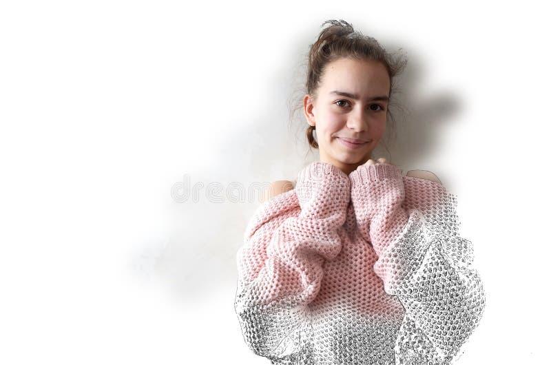 桃红色被编织的毛线衣的十几岁的女孩 库存照片