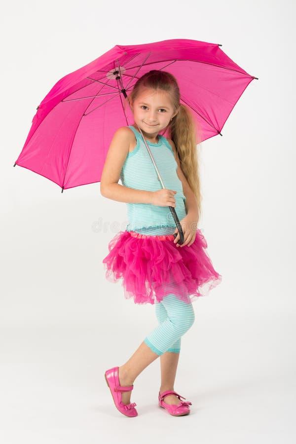 桃红色裙子的一个小女孩是冷颤的与伞 库存图片