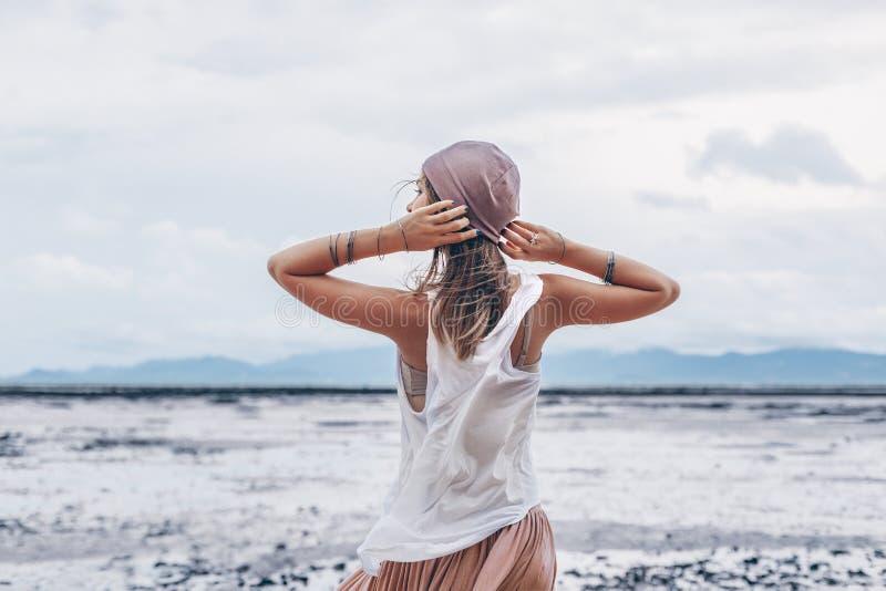 桃红色裙子的美丽的年轻时髦的妇女在海滩 免版税图库摄影