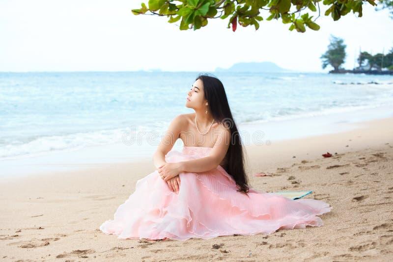 桃红色褂子的美丽的年轻女人坐夏威夷海滩 库存图片