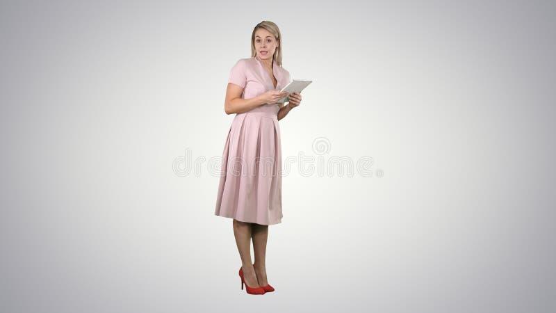 桃红色身分的女性年轻女人与片剂和给讲话在梯度背景的照相机 免版税库存照片