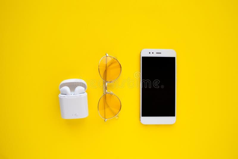 桃红色透明太阳镜、无线耳机和智能手机在明亮的黄色背景说谎 图库摄影