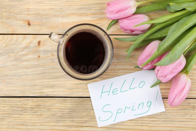 桃红色郁金香、一杯咖啡和在纸的文本你好春天美丽的花束在自然木背景 vi 免版税图库摄影