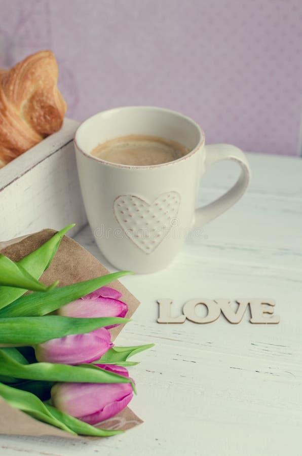桃红色郁金香咖啡用新月形面包,花束和木词爱 库存照片