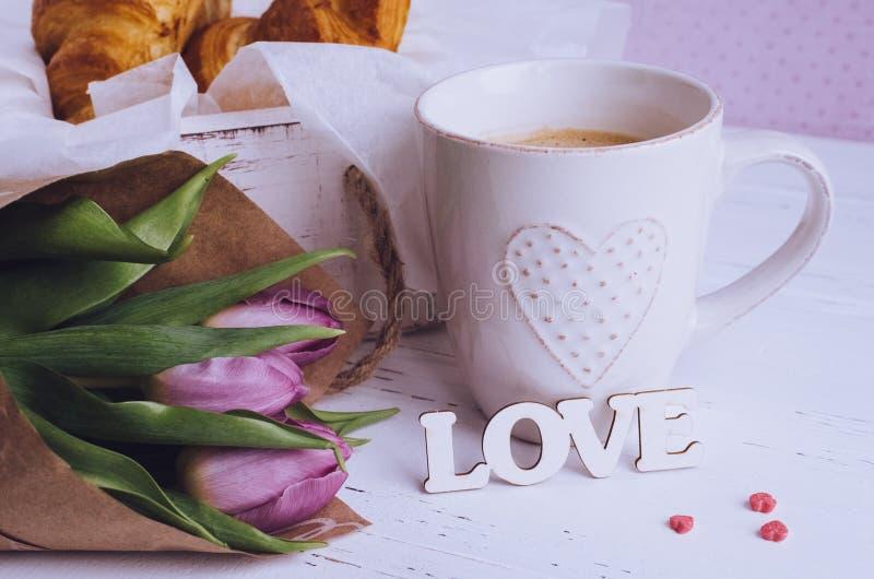 桃红色郁金香咖啡用新月形面包,花束和木词爱 图库摄影