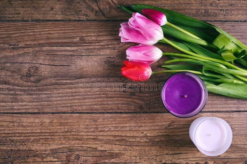 桃红色郁金香花和两cendels在土气桌上为3月8日,国际妇女天,生日,情人节或 库存照片