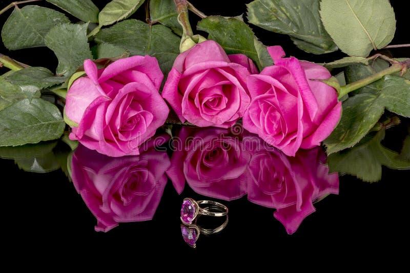 桃红色配比的圆环和玫瑰反射性表面上 库存照片