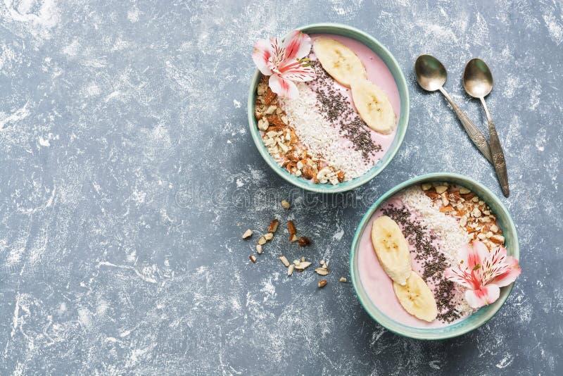 桃红色酸奶用杏仁、香蕉、chia种子和椰子剥落在蓝色碗在用花装饰的灰色背景 健康 免版税库存图片
