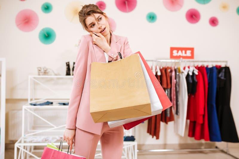 桃红色长裤套装身分与购物带来和谈话的女孩在手机在衣裳商店 免版税库存照片