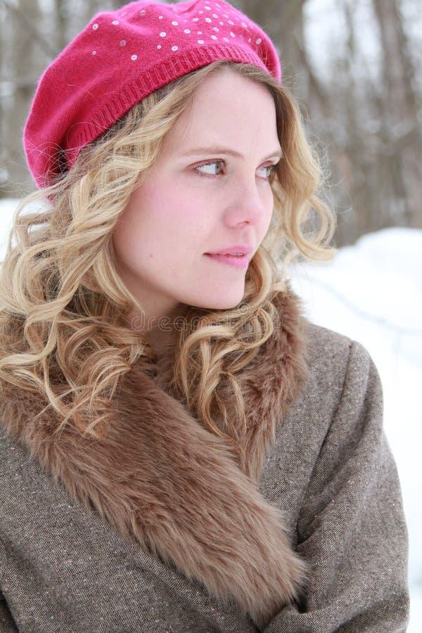 桃红色闪光金属片的贝雷帽和毛皮夹克甜甜地微笑的妇女 免版税库存图片