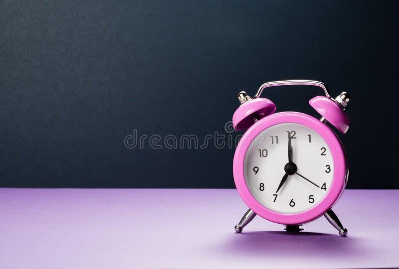 桃红色闹钟在紫色背景的早晨7点 库存图片