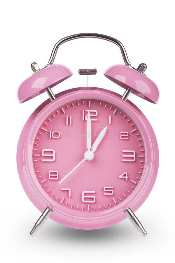 桃红色闹钟用在下午1点上午或的手 库存图片