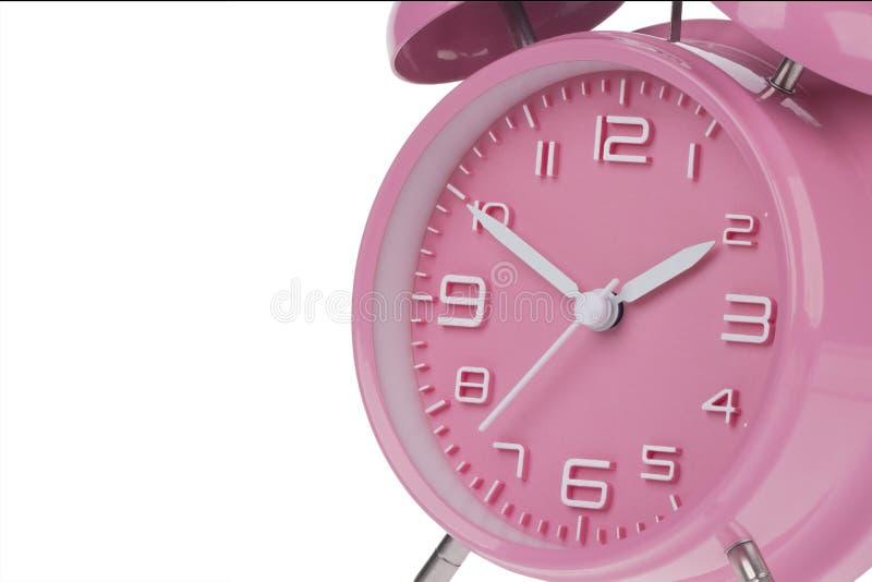 桃红色闹钟用在10和2的手 免版税库存照片